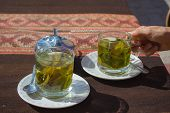 """Tea cups with Coca leaves infusion known as """"Mate de Coca"""" typical drink of local people leaving at high altitude on the Andes in Peru and Bolivia. Shot directly above with natural daylight. poster"""