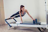 Pilates reformer workout exercises woman brunette at gym indoor. poster