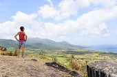Hiking woman on travel excursion during holiday cruise looking at St Kitts and Nevis landscape. Caribbean nature during summer vacations. Young girl standing at lookout looking at viewpoint. poster