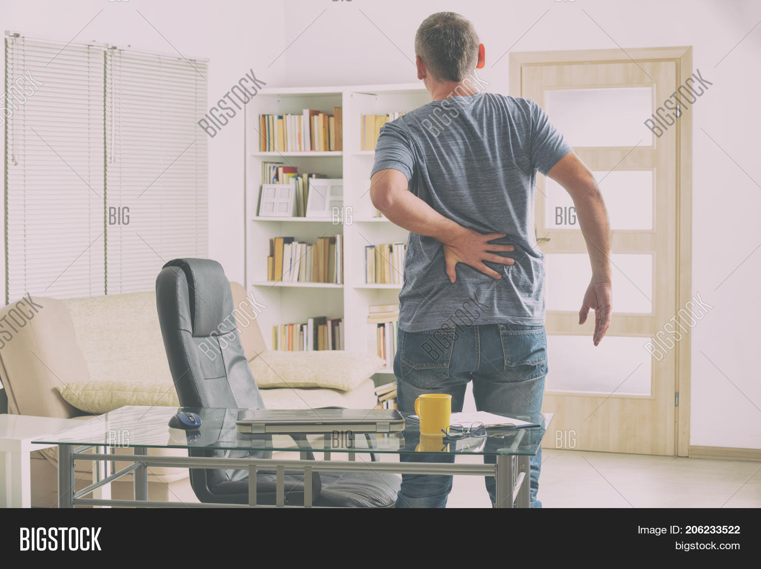 Man In Home Office Suffering From Low Back Pain Standing Near Desk With  Notebook, Papers