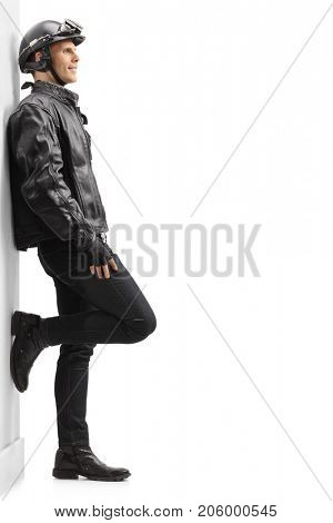 Full length profile shot of a biker leaning against wall isolated on white background
