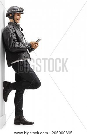 Full length profile shot a biker leaning against a wall and using a phone isolated on white background