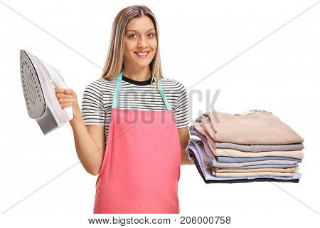 Young woman holding an iron and a pile of ironed and packed clothes isolated on white background