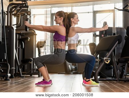 Side view of two young women smiling while exercising together back to back with weight plates in the interior of a modern fitness club