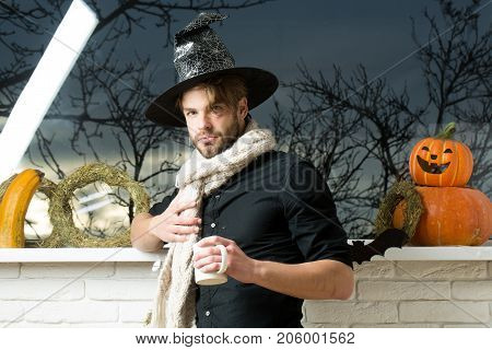 Halloween Macho wearing witch hat and scarf. Man holding cup at window with autumn trees. Magic potion concept. Warm and homely atmosphere. Holiday symbols and decorations.