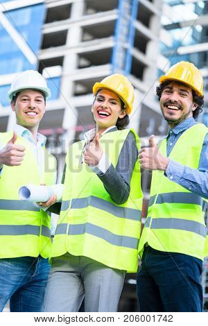 Team of civil engineers and architects at construction site giving thumbs up gesture and saying OK