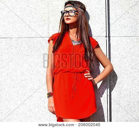 Fashion portrait of young hippie woman model in summer sunny day in bright colorful hipster clothes