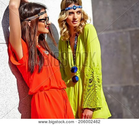 Fashion portrait of two young hippie women models in summer sunny day in bright colorful hipster clothes