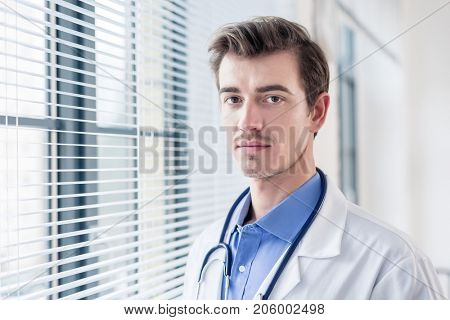 Close-up portrait of a young serious doctor looking at camera with determination and dedication in a modern hospital or medical clinic