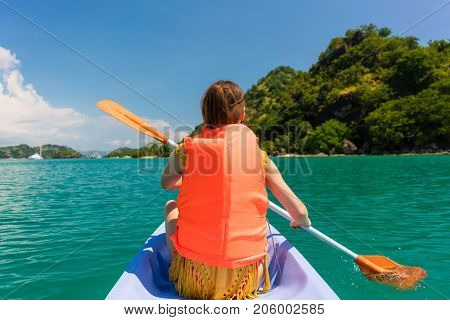 Rear view of young woman experiencing freedom while paddling in a sunny day of summer during vacation in Flores Island, Indonesia