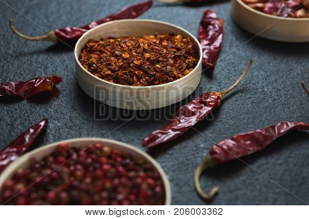 Close-up of dried red chili pepper and crushed red pepper in bowl