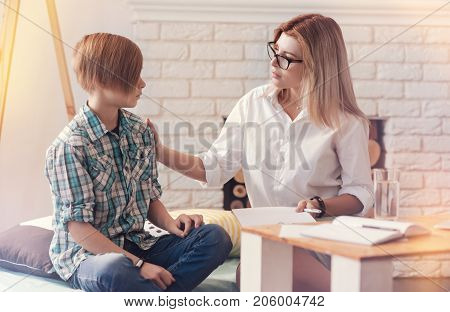 Tell me everything. Pleasant helpful psychologist talking with a troubled school boy while having a psychological session