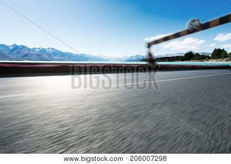 blurry emtpy asphalt road with road sign near beautiful lake in blue sky