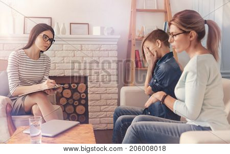 Generation gap. Professional concerned psychologist making notes and talking with a caring mother and her crying son while having a psychological session