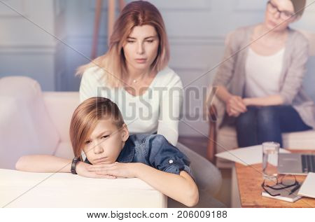 My dear. Pleasant loving mother comforting his depressed son while sitting on the ocuch and having a psychological session