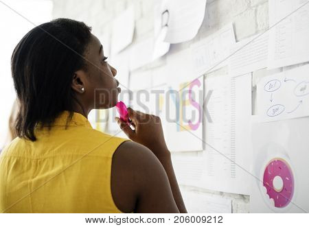 African descent woman standing thoughful infront of work bricks wall board
