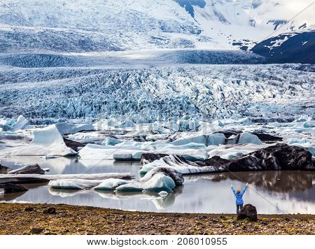 Sunset illuminates the glacier. Glacier provides water Ice Lagoon Jokulsarlon. The concept of extreme northern tourism. Woman looks at a glacier