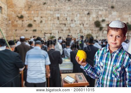 People in white Taliths pray at the Western Wall of the Temple. Beautiful Jewish boy in white skullcap, with etrog. Jewish holiday Sukkot