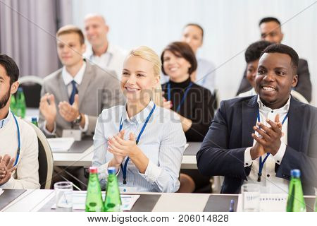 business and education concept - group of happy people applauding at international conference
