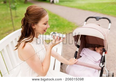 motherhood, technology and people concept - happy mother with baby girl in stroller using voice command recorder on smartphone at summer park