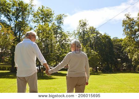 old age, retirement and people concept - happy senior couple holding hands and walking at summer park