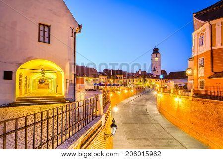 Sibiu Romania - Lesser Square and Council Tower at twilight. Transylvania saxon city.