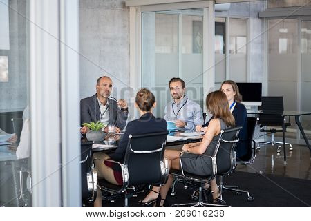 Business people sitting in boardroom and working together at new strategy plan. Group of leader and businesspeople in a meeting at office. Senior executive with his team working in a conference room.