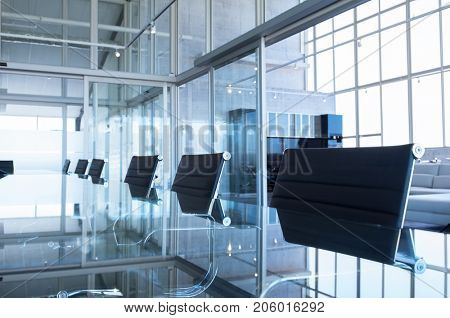 Closeup of an empty conference room before meeting. Detail of conference crystal table and black chairs in boardroom. Elegant chairs and modern table in an empty board room in office.