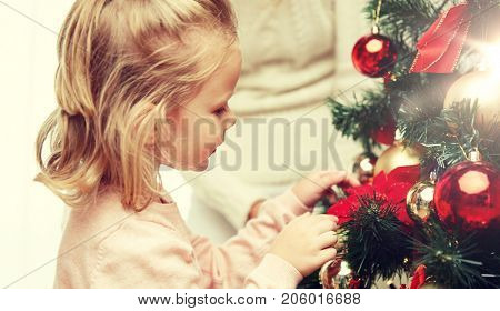 family, x-mas, winter holidays and people concept - happy  little girl decorating christmas tree  with mother at home