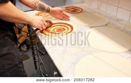 food cooking, culinary and people concept - cook or baker with spoon applying tomato sauce to raw pizza dough at pizzeria