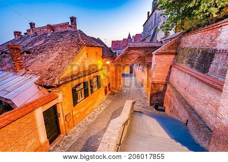 Sibiu Romania - Passage of the Stairs and the Lutheran Cathedral at twilight. Transylvania saxon city.