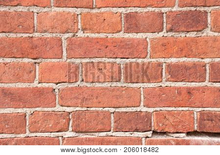 Old wall of red brick cemented in seams with cement