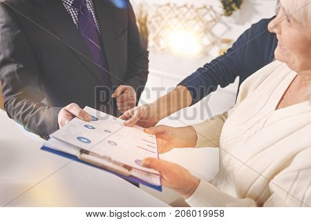 Some tips. Close up of folder in hands of a professional insurance agent while consulting positive retired couple at home