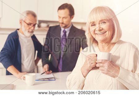 Insure your future. Positive hospitable aged woman drinking tea while her husband standing in the background with their insurance agent