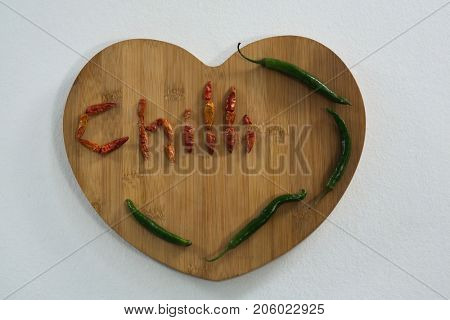 Dried red chili pepper arranged in chili text with green chili on heart shaped wooded board