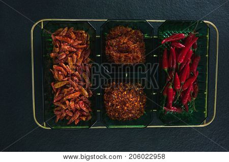 Dried red chili pepper, red chili and crushed red pepper in bowl on white background