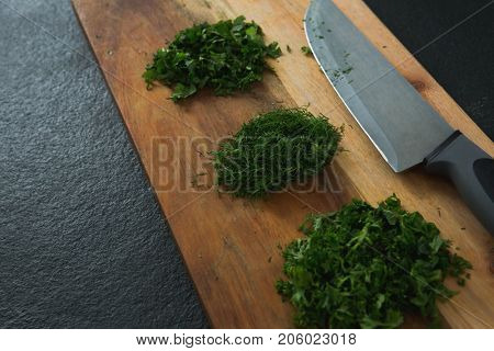 Close-up of chopped herbs with knife on chopping board