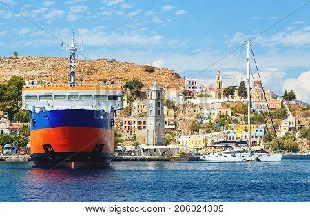 View on Greek sea Symi island harbor port, classical ship yachts, houses on island hills, tourists Aegean Sea bay.
