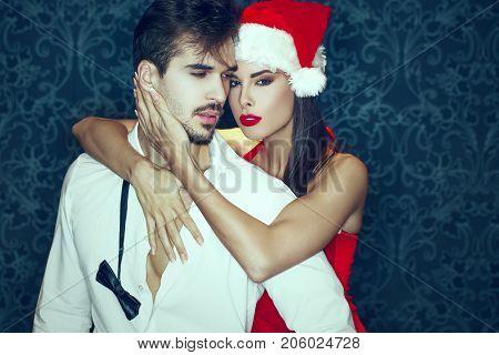 Passionate couple at Christmas sexy santa woman and rich man