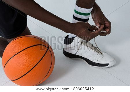 Low section of basketball player tying shoelace on white background