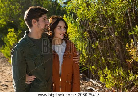 Young couple with arms around standing by trees