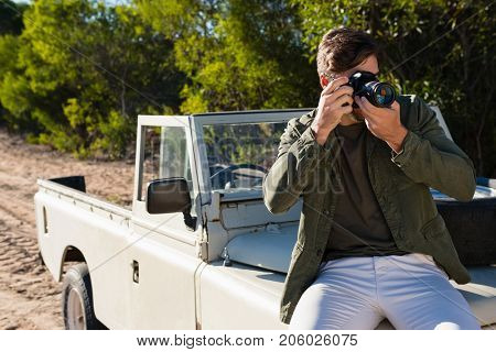 Young man photographing while sitting on vehicle hood at field