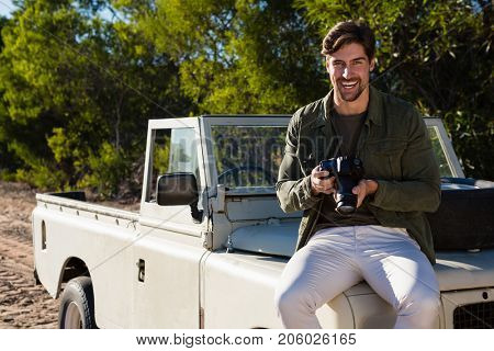 Portrait of smiling man with camera on vehicle hood at field