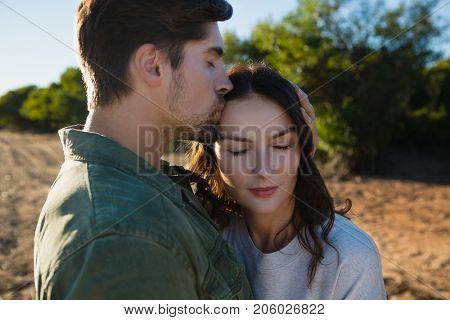 Young man kissing woman with eyes closed, on landscape