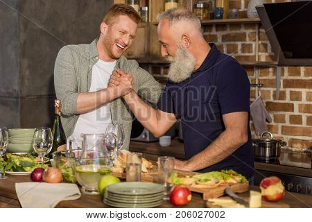 Father And Son Arm Wrestling Together
