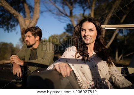 Portrait of confident woman sitting in vehicle during safari vacation