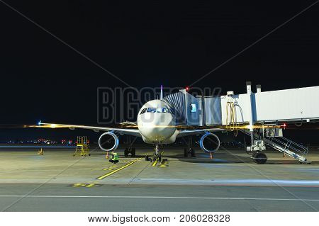 Modern white passenger airplane standing on parking place at night and get ready for boarding passengers at international airport.