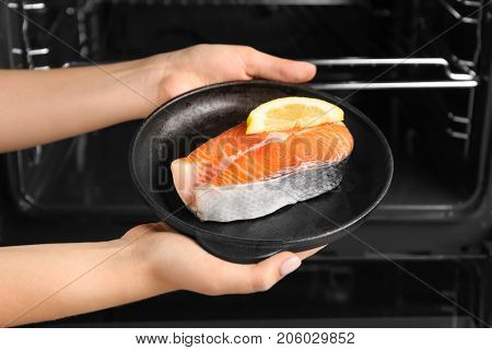 Woman holding salmon steak with lemon in portioned frying pan near oven