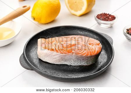 Salmon steak in portioned frying pan on white table