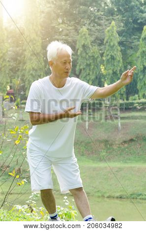 Portrait of healthy grey hair Asian old man practice wushu at outdoor park in morning.
